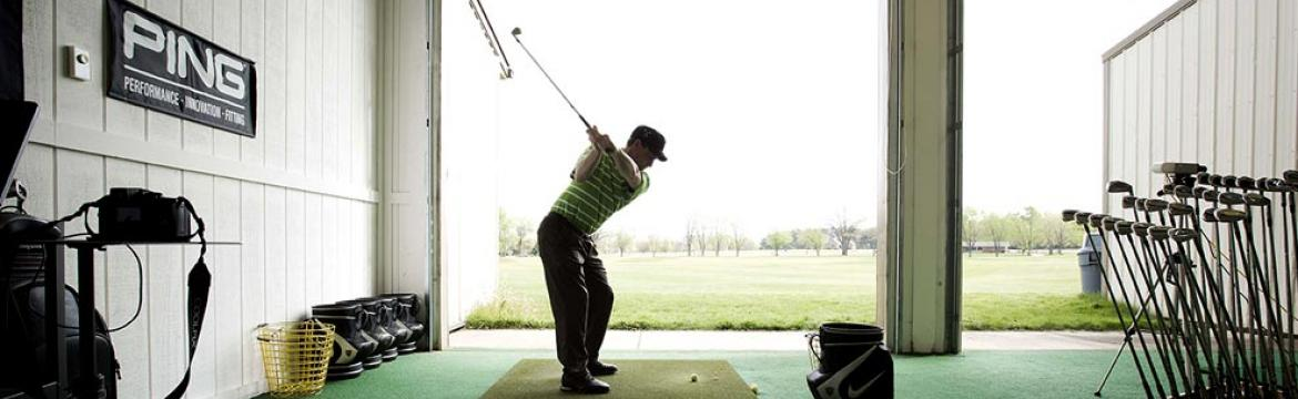 a golfer uses the practice facility at Swan Lake